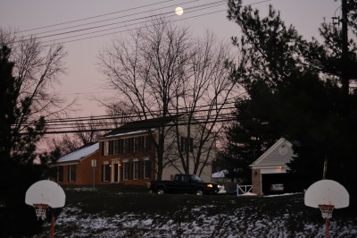 Full moon creates triangle with basketball nets in a quiet, wintry neighborhood in Maryland, USA.