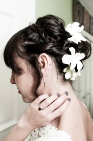 Woman with flowers in her hair, touches her neck and shows her engagement ring.