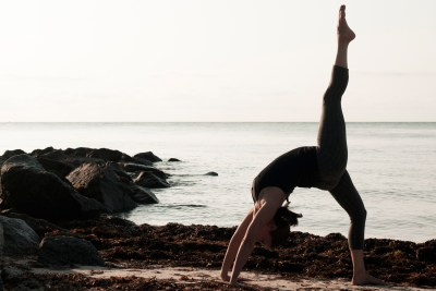 Woman on the beach in wheel pose with one leg extended.