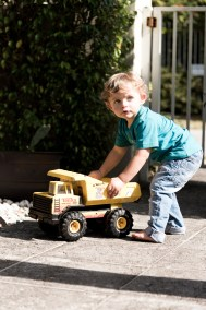Blond boy playing with a metallic, yellow truck.