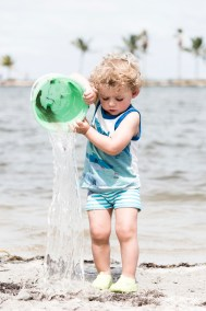Curly, blond toddler pouring a bucket of water at the beach in Matheson Hammock Park in Miami.