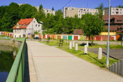 Colorful garage doors, panelák buildings, and a pond in the Czech Republic.