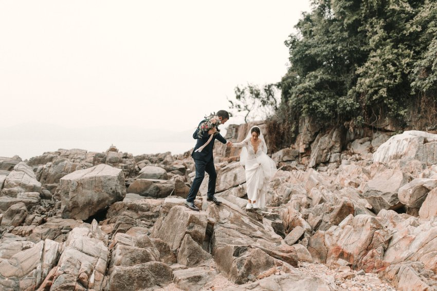 Hong Kong Wedding Photographer Natalie Pluck captures the beautiful wedding of Veronica and Steve. Lace wedding dress with plunging illusion neckline and detachable train. Festoon lighting for a romantic evening reception by candlelight. Fine art Wedding Photography dream wedding inspiration. Wedding reception at one thirty-one in Sai Kung. Unique portraits by lobster bay on the rocks by the sea. Navy suit and purple bow tie for this relaxed groom. Timeless wedding style, chic up do. Pink bouquet inspiration. Photographed by Natalie Pluck. To see more of this wedding click the link: http://www.nataliepluck.com/hong-kong-wedding-photographer #hongkongweddingphotographer #saikungweddingphotographer #hongkongwedding #veronicalamwedding #saikungwedding #onethirtyone #timelessweddinginspiration #kowloonwedding #hkwedding #bertaweddingdress #bertawedding #detatchabletrain #nataliepluck #dreamweddinggown #weddingdressgoals #relaxedweddingphotography #laidbackweddings