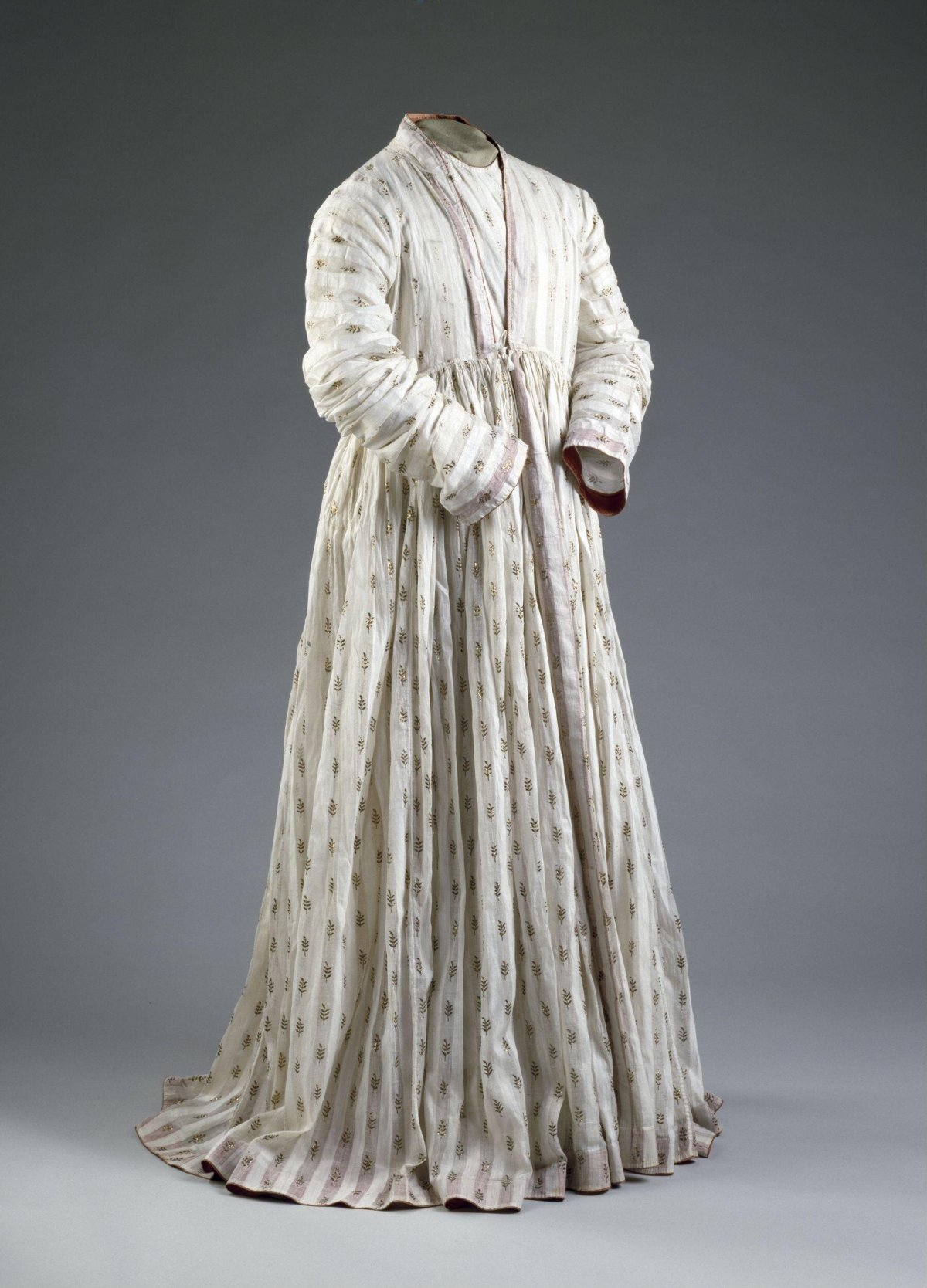 Man's robe (Jama) of white cotton muslin embroidered with gold. Woven in vertical stripes, alternately clear and opaque. The clear stripes are patterned at regular intervals with sprigs of gold foil, applied to the face of the material and stitched down on the reverse with white thread. The hem, collar, cuffs and other borders are faced on the inside with red satin.