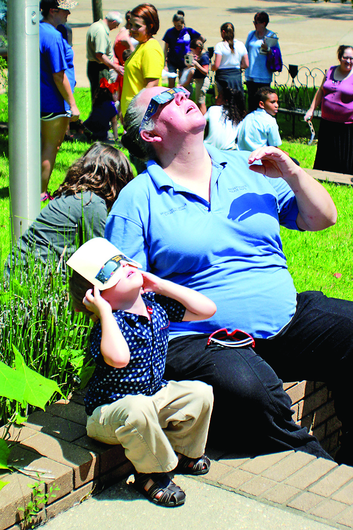 Jack and Sara Dunn sit on the steps of the library to view the eclipse. Photo by Ashley Froust