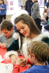 Belle Hope Rachal makes crafts with two guests at one of the crafts tables.