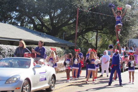 NSU President Dr. Chris Maggio and First Lady Jennifer Maggio, followed by NSU Cheerleaders.