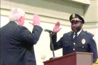 Clerk of Court David Stamey administers the Oath of Office to Police Chief Nikeo Collins. Images by Juanice Gray