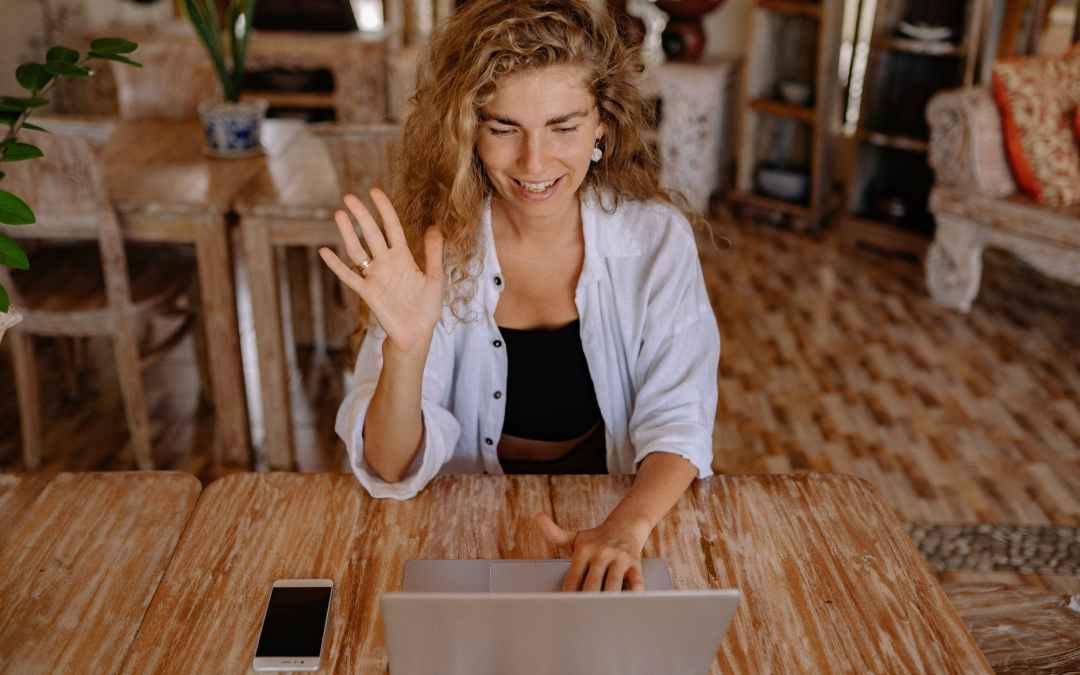 photo of woman saying hi through laptop