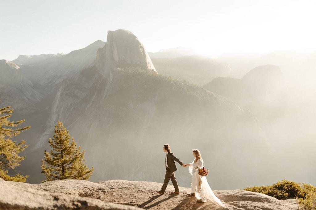 Couple holds hand and walks along yosemite overlook