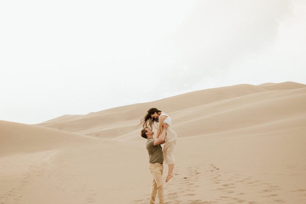 Couple embraces at great sand dunes engagement session
