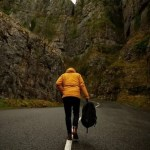woman-walking-up-road-in-mountains