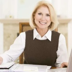 Woman-in-dining-room-with-laptop-and-paperwork-smiling