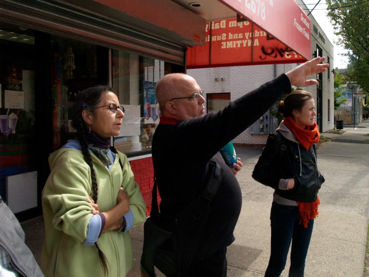 Smith Hill Saunter: Walk Leader John Chiafalo gestures toward an empty lot across the street from an Asian-American market.