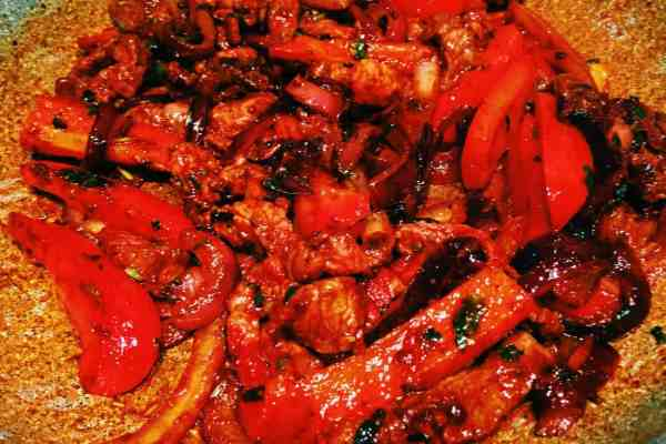 Ribeye added to tomato corinader stalks and red onion Mexico fajitas nationaldish