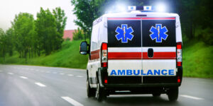 This image shows an ambulance with flashing lights driving on a highway