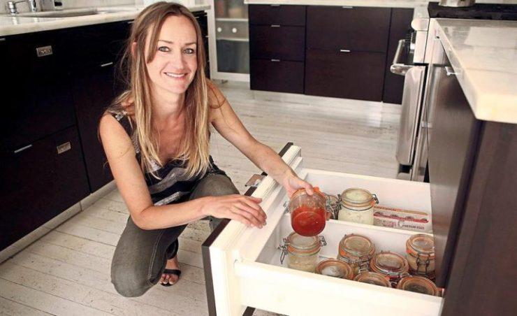bea johnson nella propria cucina: apre un cassetto mostrando i barattoli in vetro in cui conserva le proprie scorte alimentari.
