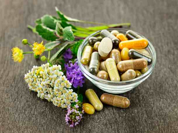 supplement pills in a glass bowl next to some herbs