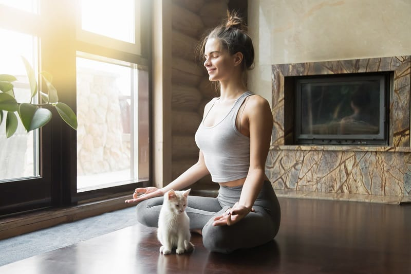 woman meditating with a cat in front of her