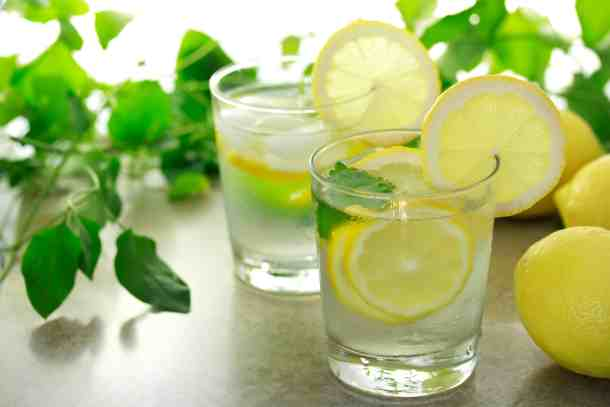 lemon water in glasses with lemon wedges and mint