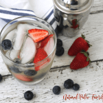 patriotic paleo margarita with silver shaker cup, strawberries, and blueberries