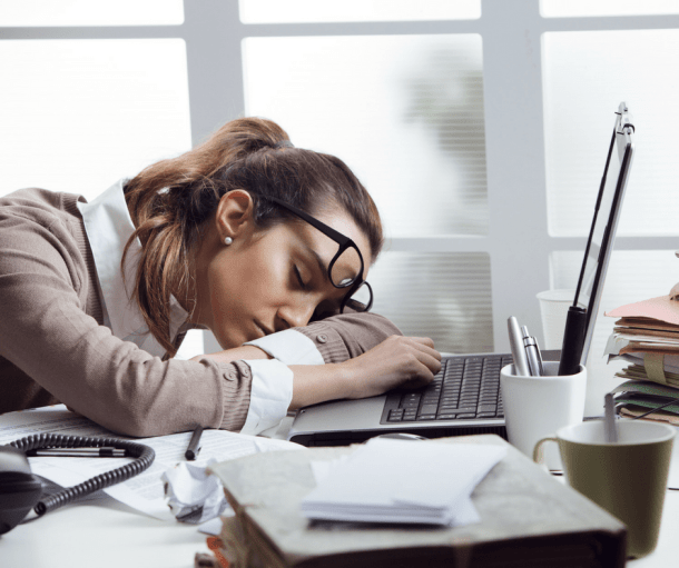 woman sleeping on her desk with laptop open