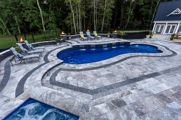 Grey travertine pool copings around spa San Jose