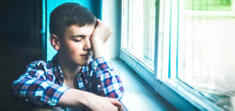 Photographie d'un adolescent qui se tient la tête dans les mains en raison de son hypersensibilité électromagnétique.