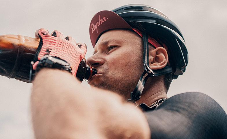 Homme cycliste qui boit une boisson protéinée et riche en calorie pour grossir vite et prendre de la masse après le sport