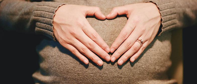 Mains jointes qui forment un cœur sur le ventre d'une femme qui attend un bébé durant sa grossesse.