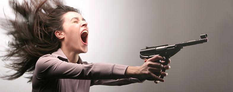 Femme stressée qui crie et qui veut tirer au pistolet pour évacuer son angoisse et sa colère