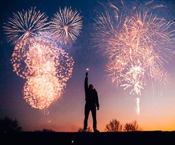 Photographie d'un homme devant un feu d'artifice pour symboliser l'éjaculation et une sexualité épanouie sans impuissance et problèmes d'érection