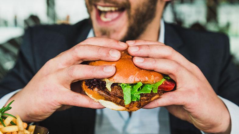 Un homme qui s'apprête à prendre son repas et à croquer dans un gros hamburger