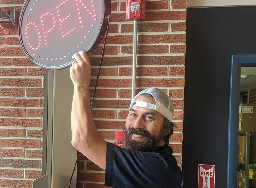 Man standign with open sign in front of Zhills Brewing