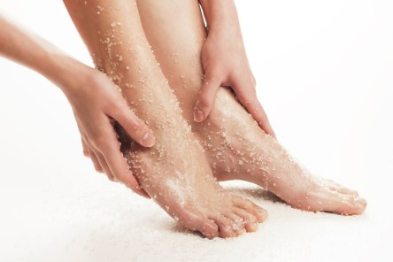 Woman rubbing scrub into feet, white background, feet and hands only