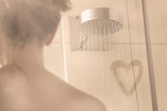 Woman in a shower, steamed up with heart drawn with finger