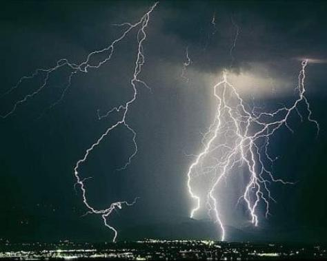 A photograph showing some spectacular lightning bolts above a city skyline at night.