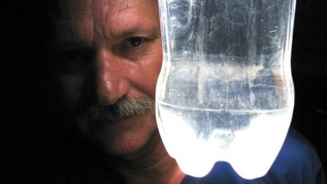A close-up photograph of Alfredo Moser in the light of the bottle lamp - his makeshift invention.