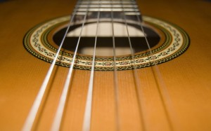 A close-up photograph of a classical acoustic guitar's sound hole with Rosette display and nylon strings above.