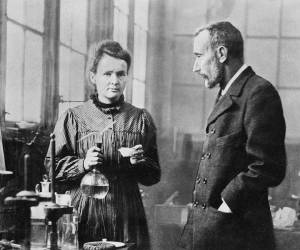 An old black and white photograph showing Marie and Pierre Curie in their lab.