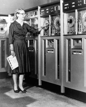 A photograph showing Grace Hopper standing in front of an old-fashioned mainframe computer.