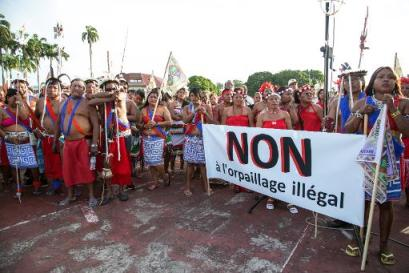 """A photograph showing a group of protesters demonstrating against illegal placer mining in French Guyana. Their sign reads: """"Non à l'orpaillage illégal."""""""