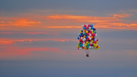 A photograph showing a huge mass of helium balloons carrying their human payload up into the sunset sky. Image: Jonathan Frappe