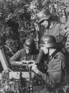 A black and white WW2 photograph showing German soldiers operating an Enigma machine.