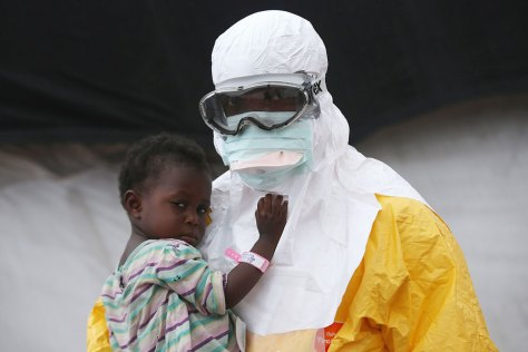 A photograph showing one of the containment-suited Ebola doctors caring for a yound victim of the illness during the Liberia epidemic in 2014.