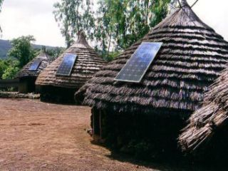 A photograph showing small solar panels installed on thatch-roofed huts in Kenya.