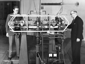 A black and white photograph showing Jack Parry and Louis Essen standing next to the World's first caesium-133 atomic clock.