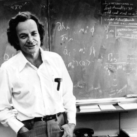 A black and white photograph of Nobel physicist Richard Feynman, pictured smiling in front of the blackboard of a lecture room, which is covered with mathematical equations.