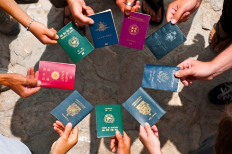 Young international physicists holding out their passports - most of them from different nations.