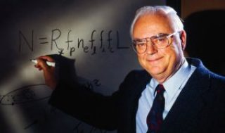 A photograph of Frank Drake, posing in front of his equation written on a white board.